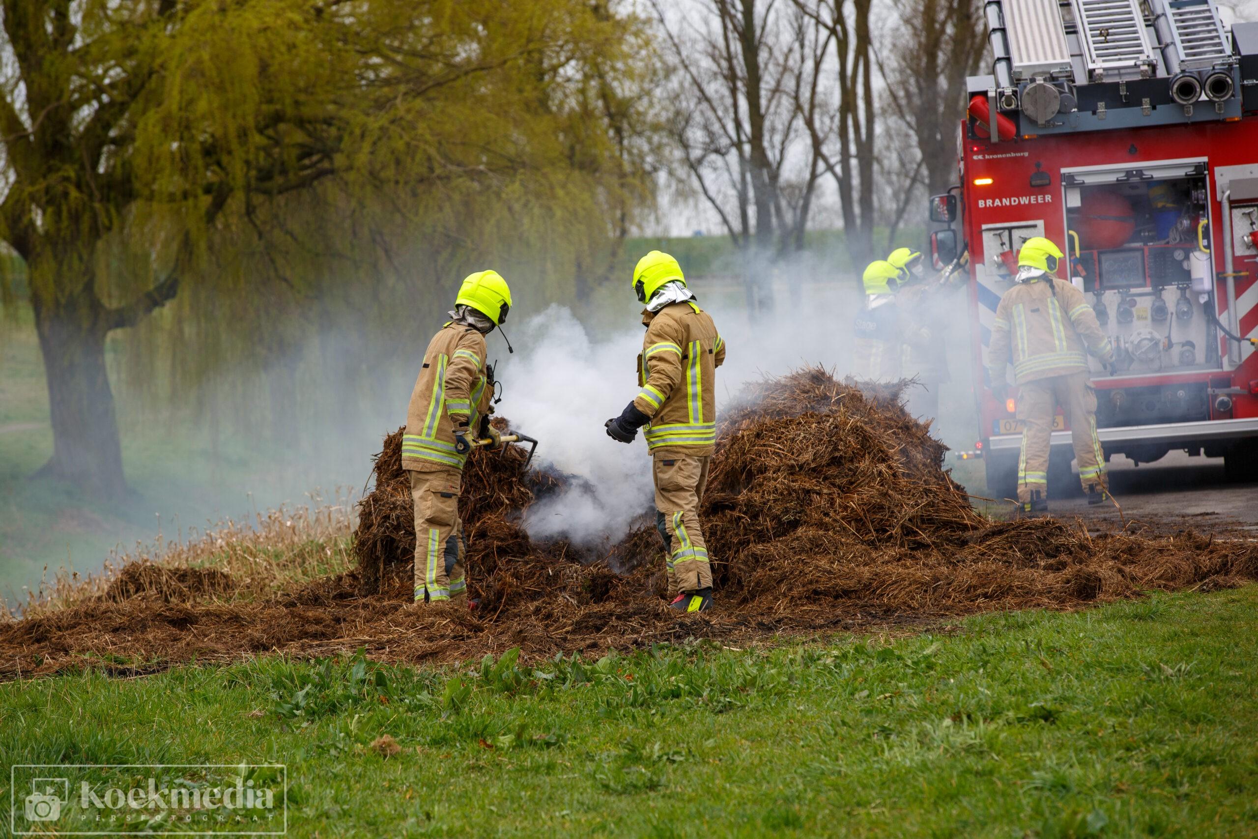 Brandweer blust broei in berg rietafval