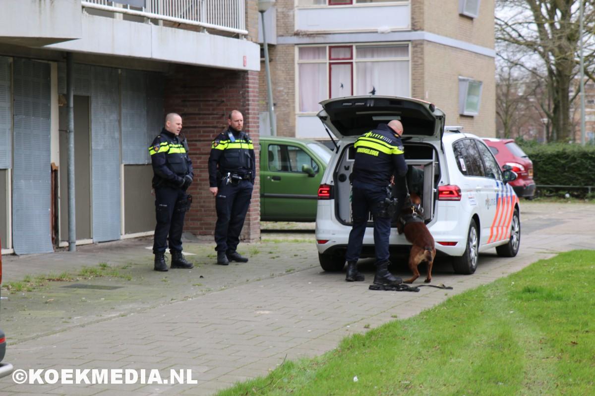 Politie doorzoekt gebied tussen flats Parkweg Schiedam.